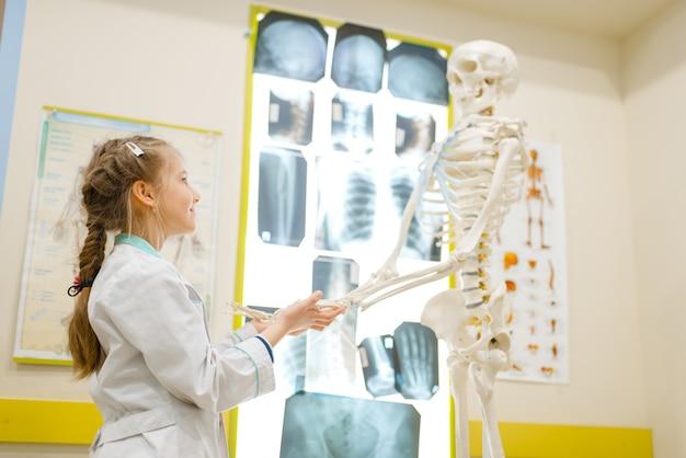 Kleines mädchen in uniform, das doktor mit menschlichem skelett spielt
