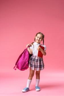 Kleines mädchen in uniform mit rucksack und notizbuch