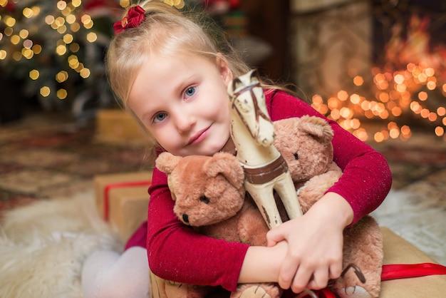 Kleines mädchen in weihnachten mit spielzeug, glückliches kind hautnah
