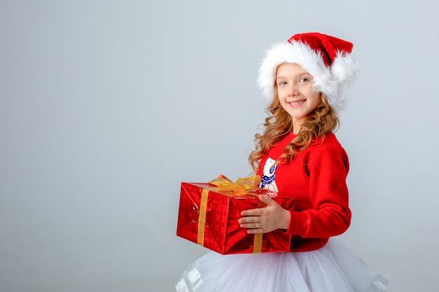 Kleines mädchen in weihnachtsmütze mit geschenk auf weißem hintergrund