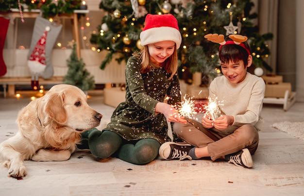 Kleines mädchen in weihnachtsmütze und junge mit rentierhörnern, die wunderkerzen halten, während sie zu hause neben golden retriever hund sitzen
