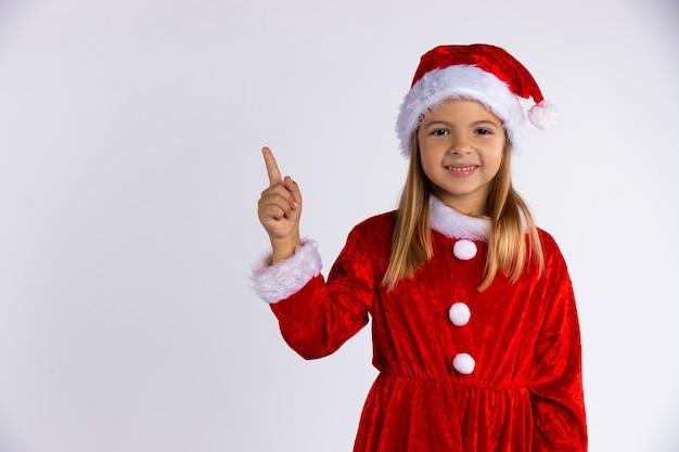 Kleines mädchen in weihnachtsmütze und kostüm mit schönem lächeln zeigt auf den finger. auf weiß isoliert