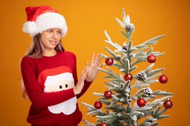 Kleines mädchen in weihnachtspullover und weihnachtsmütze, das neben einem weihnachtsbaum steht und ihn unzufrieden ansieht, hält die hände über orangefarbenem hintergrund aus