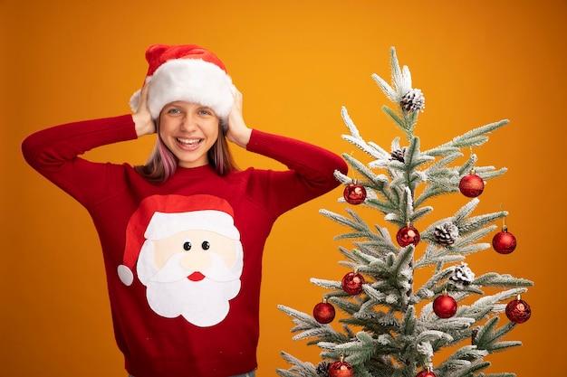 Kleines mädchen in weihnachtspullover und weihnachtsmütze, die ohren mit händen mit verärgertem ausdruck bedeckt, neben einem weihnachtsbaum auf orangefarbenem hintergrund stehend