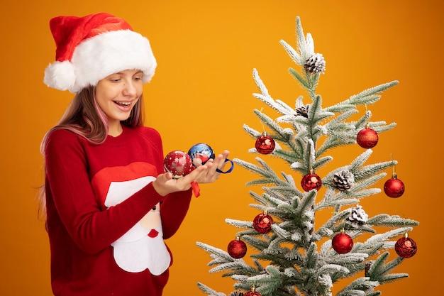 Kleines mädchen in weihnachtspullover und weihnachtsmütze mit bällen, die sie mit einem lächeln auf dem gesicht betrachten, das neben einem weihnachtsbaum auf orangefarbenem hintergrund steht standing