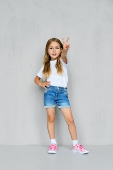Kleines mädchen in weißem t-shirt, jeansshorts und rosa turnschuhen stehend zeigt v-zeichen