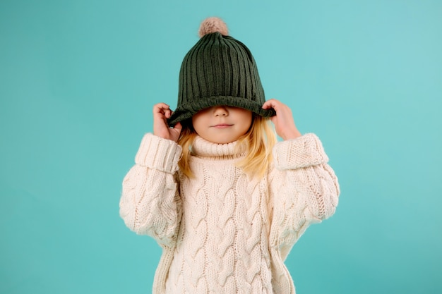 Kleines mädchen in wintermütze und pullover auf blau