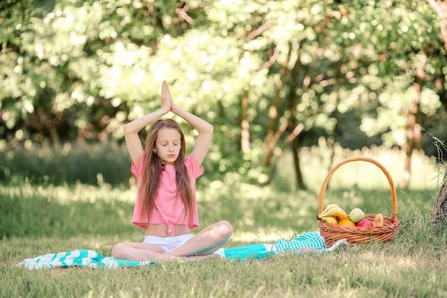 Kleines mädchen in yogaposition im park,