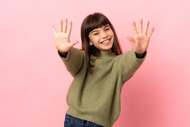 Kleines mädchen isoliert auf rosa hintergrund, das mit den fingern zehn zählt
