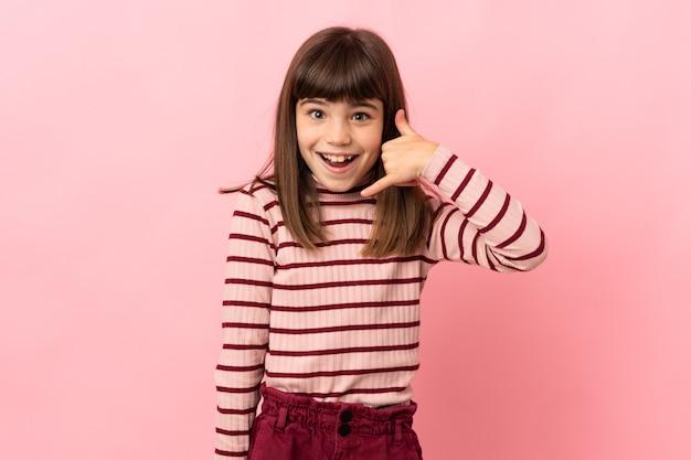 Kleines mädchen isoliert auf rosa hintergrund, das telefongeste macht. ruf mich zurück zeichen