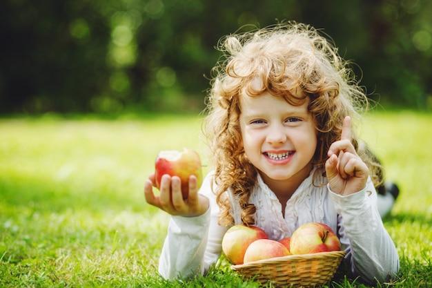 Kleines mädchen isst apfel und lächelt, weiße zähne zeigend.