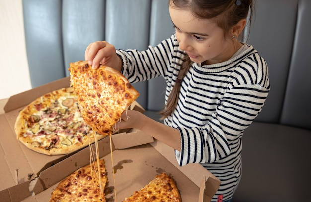 Kleines mädchen isst appetitliche käsepizza zum mittagessen.