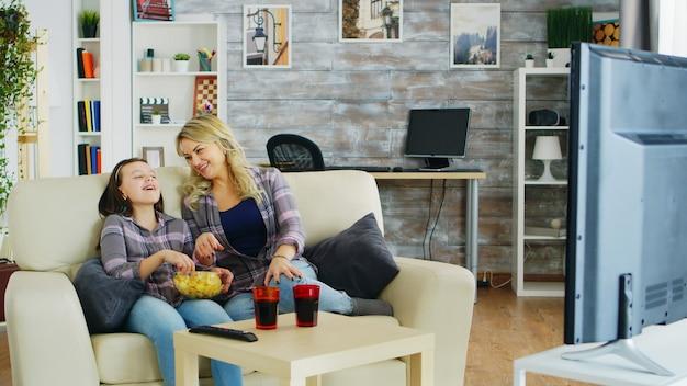 Kleines mädchen isst chips beim fernsehen mit ihrer mutter, die auf der couch sitzt.