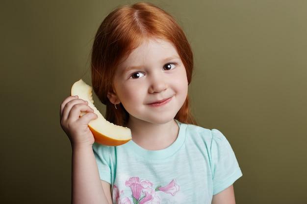 Kleines mädchen isst eine melone auf einem grünen hintergrund, helle nette gefühle auf dem gesicht des mädchens, melone in den händen einer jugendlichen, die kindgrimassen und -haltungen.