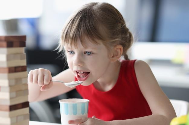 Kleines mädchen isst eis mit löffel aus plastikbecher zu hause gesundes babynahrungskonzept