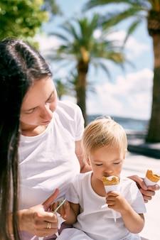 Kleines mädchen isst eis, während sie auf dem schoß ihrer mutter in einem café sitzt