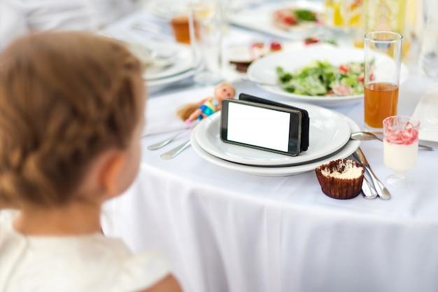 Kleines mädchen isst, während es den film auf dem tablett sieht. kind, das telefon benutzt, zeichentrickfilme, süchtig machendes spiel und zeichentrickfilm sieht