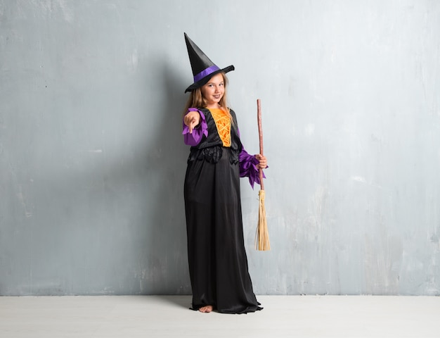 Kleines mädchen kleidete als hexe für halloween-feiertage an, die auf die front zeigen
