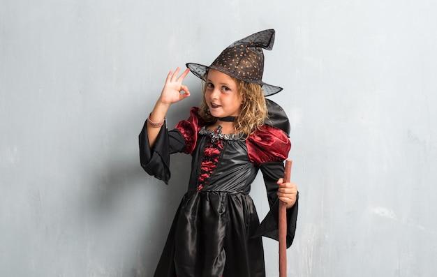 Kleines mädchen kleidete als hexe für halloween-feiertage an und macht okayzeichen