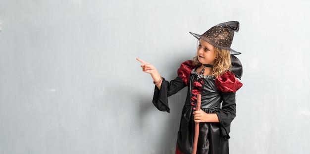 Kleines mädchen kleidete als hexe für halloween-feiertage an und zeigte auf das seitliche