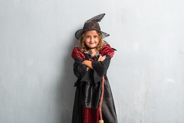 Kleines mädchen kleidete als hexe für halloween-feiertage mit ihren gekreuzten armen an