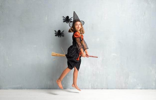 Kleines mädchen kleidete als hexe für halloween-feiertage oben auf dem besen und dem fliegen an