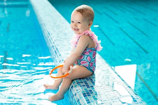 Kleines mädchen lacht im pool bei einer schwimmstunde.
