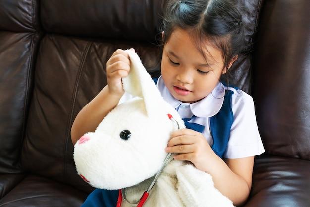 Kleines mädchen lächeln und doktor mit stethoskop spielend. kind und gesundheitskonzept.