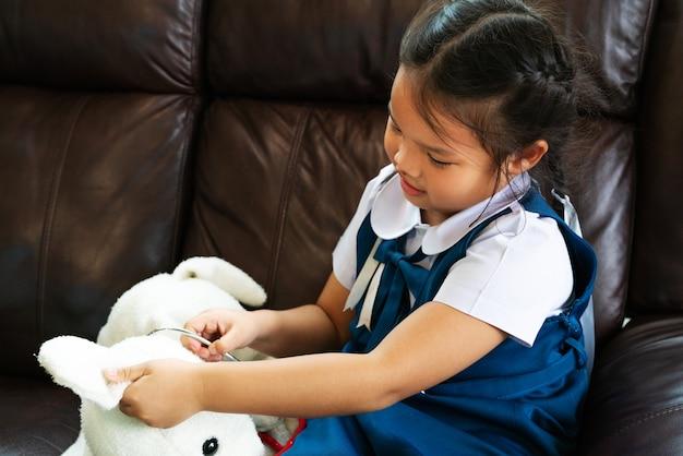 Kleines mädchen lächeln und doktor mit stethoskop spielend.