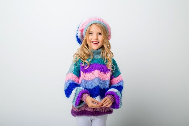 Kleines mädchen lächelnd in strickmütze und pullover auf weißem isolat
