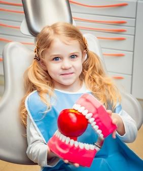 Kleines mädchen lächelnd, mit zahnersatz in der zahnarztpraxis