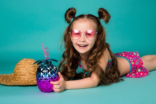 Kleines mädchen lächelt in sonnenbrille und strohhut und liegt in einem badeanzug auf einem blauen raum. glückliches kind im sommer, platz für text