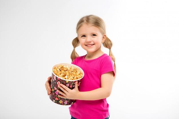 Kleines mädchen lächelt mit einem eimer popcorn