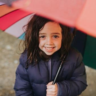 Kleines mädchen lächelt mit einem regenschirm während eines familienausflugs im freien porträt outdoors