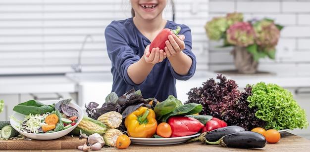 Kleines mädchen lächelt und hält paprika in ihrer hand, während salat auf unscharfem hintergrund zubereitet.