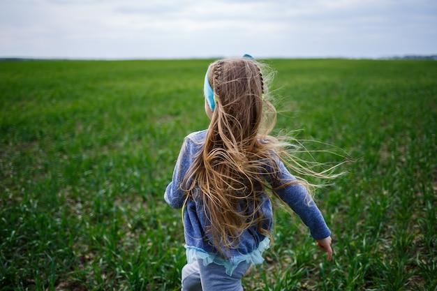 Kleines mädchen läuft auf grünem gras auf dem feld, sonniges frühlingswetter, lächeln und freude des kindes, blauer himmel mit wolken