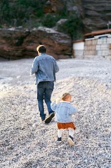 Kleines mädchen läuft hinter papa auf dem kieselstrand vor dem hintergrund der rückansicht der felsigen berge her