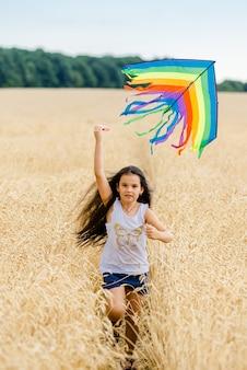 Kleines mädchen läuft im sommer auf einem weizenfeld mit einem drachen. gut geplantes und aktives wochenende. glückliche kindheit.