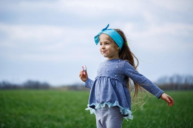 Kleines mädchen läuft und springt, grünes gras auf dem feld, sonniges frühlingswetter, lächeln und freude des kindes, blauer himmel mit wolken