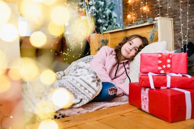 Kleines mädchen legte sich zu weihnachten und neujahr unter eine warme decke, dekorierter innenraum mit tannenbaum, roten geschenkboxen und magischen bokeh-lichtern