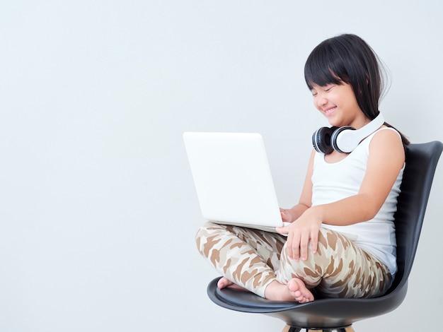 Kleines mädchen lernen online mit laptop.
