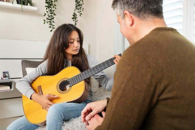 Kleines mädchen lernt gitarre spielen