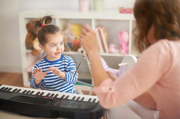 Kleines mädchen lernt klavier spielen