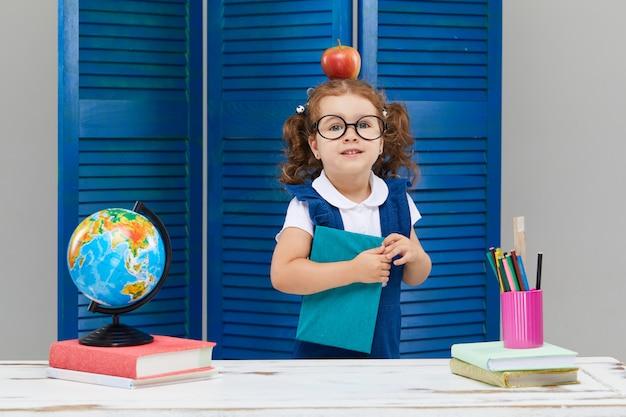 Kleines mädchen lernt, während es eine abschlusskappe trägt