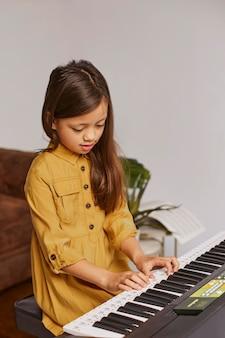 Kleines mädchen lernt, wie man die elektronische tastatur spielt