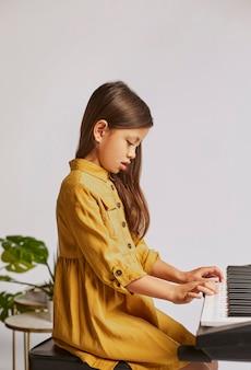 Kleines mädchen lernt, wie man zu hause elektronische tastatur spielt
