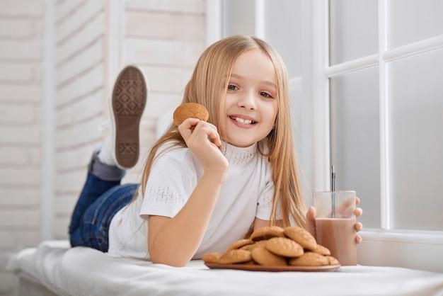 Kleines mädchen liegt auf dem fensterbrett mit keksen und schokoladenmilch