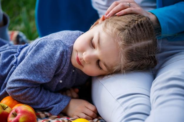 Kleines mädchen liegt auf der tagesdecke, grünes gras auf dem feld, sonniges frühlingswetter, lächeln und freude des kindes, blauer himmel mit wolken
