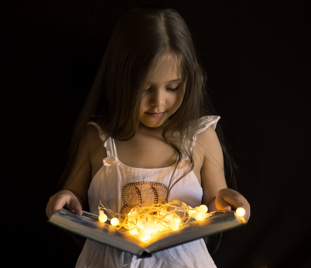 Kleines mädchen liest ein magisches buch