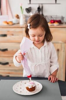 Kleines mädchen macht cupcake